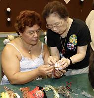 手まりの作り方を習うハワイアン。日本からの先生が丁寧に教えてくれます。