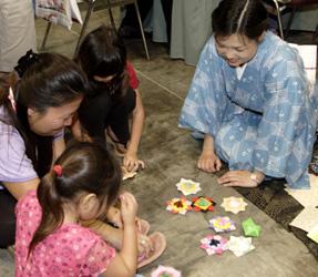 鶴やかえる、お花の形など、珍しい折り方なども教えてくれる折り紙教室の皆さんと子供たち。