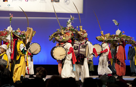 Colorful costumes and a variety of musical  instruments create a dramatic stage presentation.