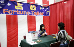 Uranai Corner, fortune telling, first time at the Honolulu Festival. The person having her palm read is quite serious!