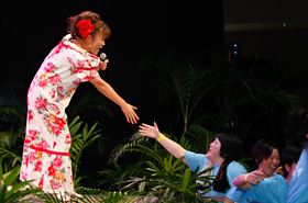 Yamada Kuniko shakes hands with a member of the audience as she sings her song.