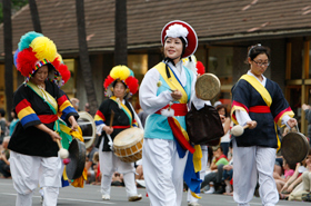 The folk music and dance of Korea performed by The Korean Traditional Music Association of Hawaii. Their taiko and dora (small gong) resonate.