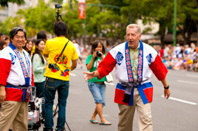 """Mayor of Honolulu Peter Carlisle decides to walk the Grand Parade and """"talk story"""" with the spectators instead of riding his convertible. President of the Honolulu Festival Foundation, Keiichi Tsujino, on the left."""