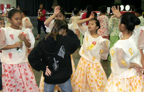 The students learn a Filipino dance from the performers. They are all children, quick friendships made!