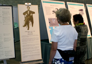 Attendees read each panel of the Joseph Heco exhibit
