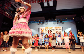The children of Hawaii perform with Momoi on stage.