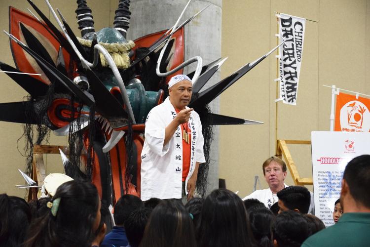 毎年、最終日のグランドパレードでオオトリを務める大蛇山。頭部のみでもその迫力たるや学生や子供たちに興味を持たせずにはいられません。 火を吹く大蛇(ホノルル大蛇山を支援し、大蛇山を世界に発信する会)は福岡県大牟田市からやってきました。民話によると大蛇は農地を潤し、子供の健康を守る水の神と言われています。